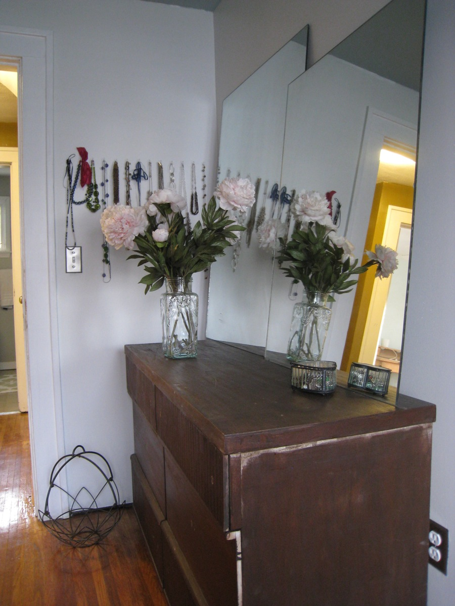 Still-to-be-refinished-dresser, faux-Peonies, unframed mirrors, and necklace hooks.