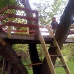 Handy-girl showing off her new treehouse.