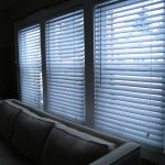 Living room blinds, partially opened, letting in a soft morning light.