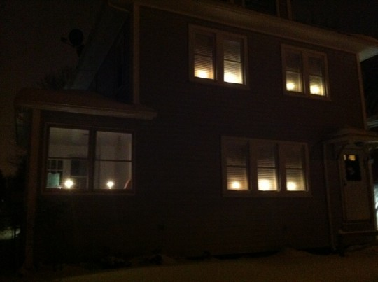 Candles in the front windows. Lots of extra reflection off the white blinds inside.