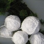 Yarn snowballs on one of the wreaths.