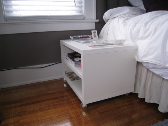 Bedroom side table. From the front, it appears to be a flat plain surface, but the shelves face to the side so I can hide books and magazines.