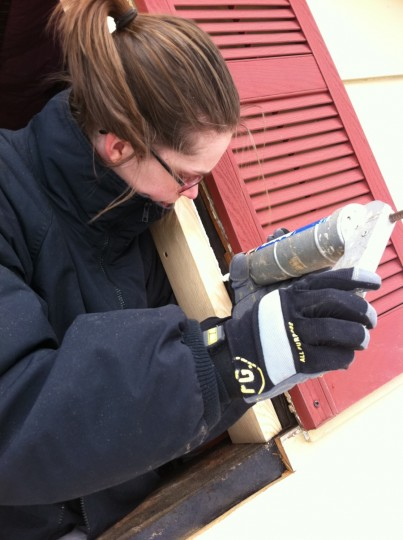 Caulking some openings from the outside prior to installing the window.