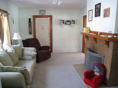 Living Room with the seller's furniture. That door? It separates the living room and the sunroom. Discolored and ugly.