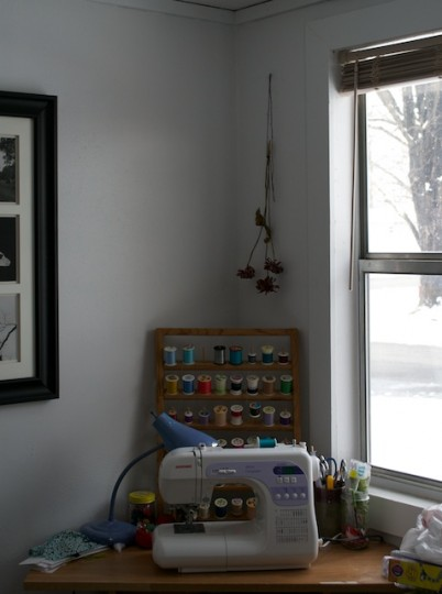 One corner of the studio shows an organized display of threads.