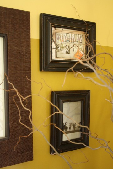 Frames with Anthropologie tear sheets seen through the curly willow branches.