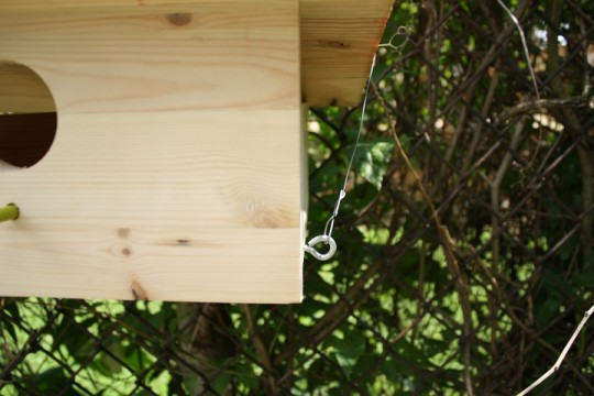 Close-up of the birdhouse hook and wire. This is installed on both sides to keep the house level.
