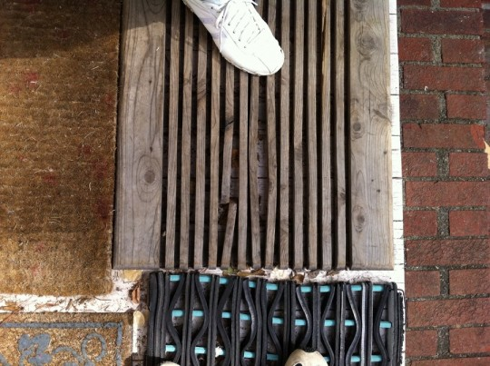Stranger's foot and a wooden slatted doormat.