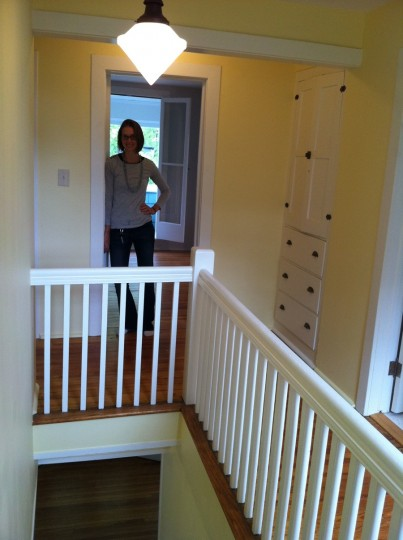 Me, upstairs in the blue cottage. Tall ceilings, built-ins, refinished railings, and antique light fixtures.