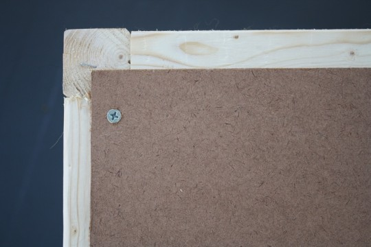 Attaching the backer board to the ottoman frame.