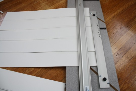 Taping together strips of paper to create a textured background for the picture frame.