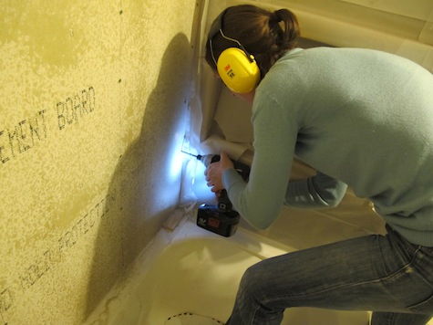 Securing cement board to a shower surround before installing tiles.