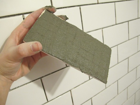 Buttering the back of subway tiles before installing in a bathroom shower.