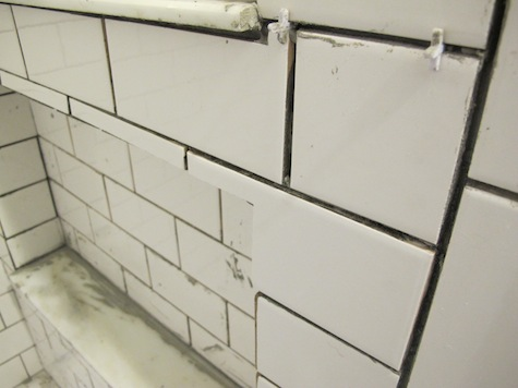 Custom cuts on subway tiles to accommodate bathroom shower shelves.