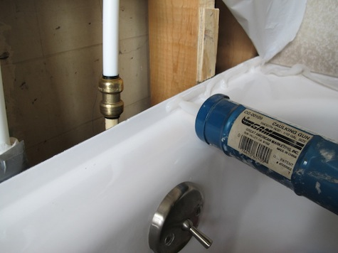 Silicone seal to adhere moisture barrier to the bathtub.