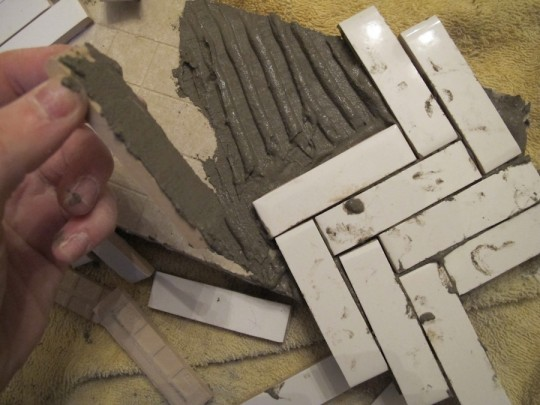 Installing tile scraps into a herringbone pattern.