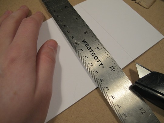 Lightly scoring the mat paper with a utility knife.