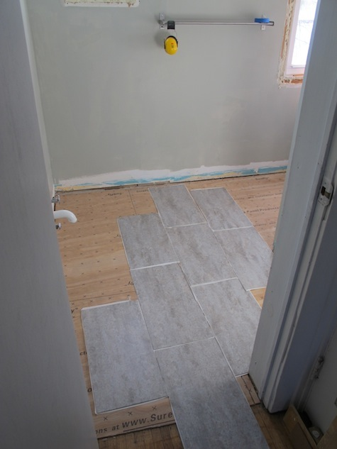 Which way should vinyl adhesive tiles be installed?