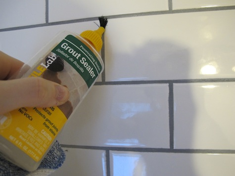 Adding grout sealer to shower to prevent absorption in new grout.