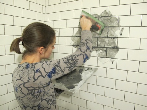 Grouting white subway tiles with pewter gray grout.