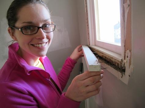 Removing window trim during a DIY bathroom remodel.