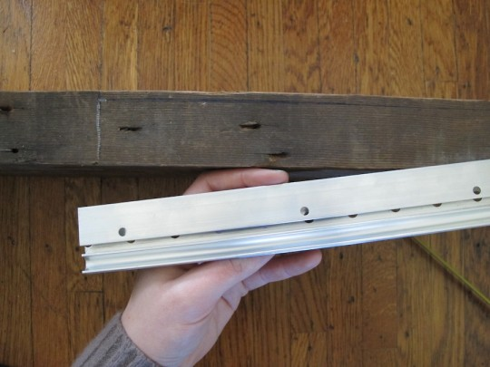 Marking where the french cleat would be attached to the edge of the shelf.