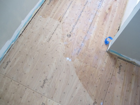 Rolling conditioner on plywood to enhance bond of vinyl tiles.
