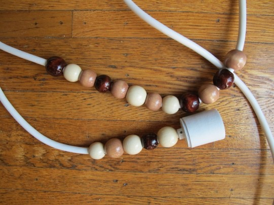 Pendant assembled with wooden beads, a socket, and an extension cord.