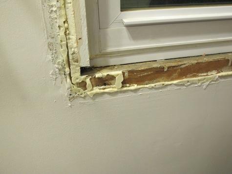 Cut away spray foam excess before putting on window trim.