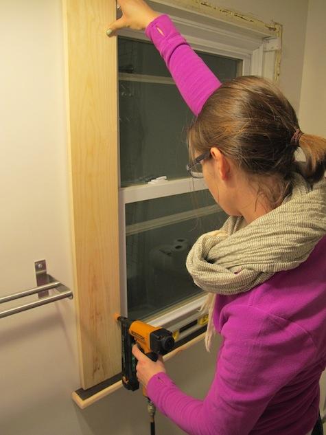Nailing DIY window trim with a nail gun.