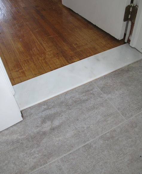 Installing a marble threshold during a bathroom remodel between vinyl and original oak floors.
