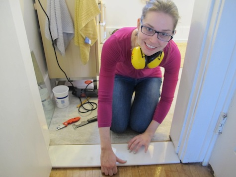 Installing a marble threshold during a bathroom remodel.