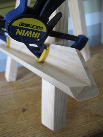 Clamping a piece of corner guard onto the easel legs.