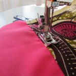Sewing together two complimentary pieces of fabric to form one of the four pillow seats.
