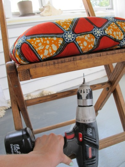 Predrill and screw into the bottom of the seat, with the cushion perfectly positioned and held in place with your hand.