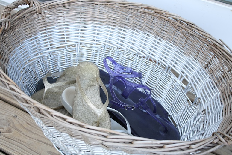 Basket filled with sandy beach shoes.