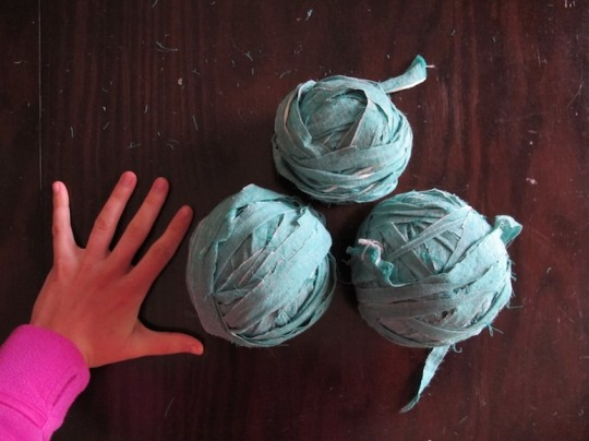 Making balls of yarn out of a piece of fabric.