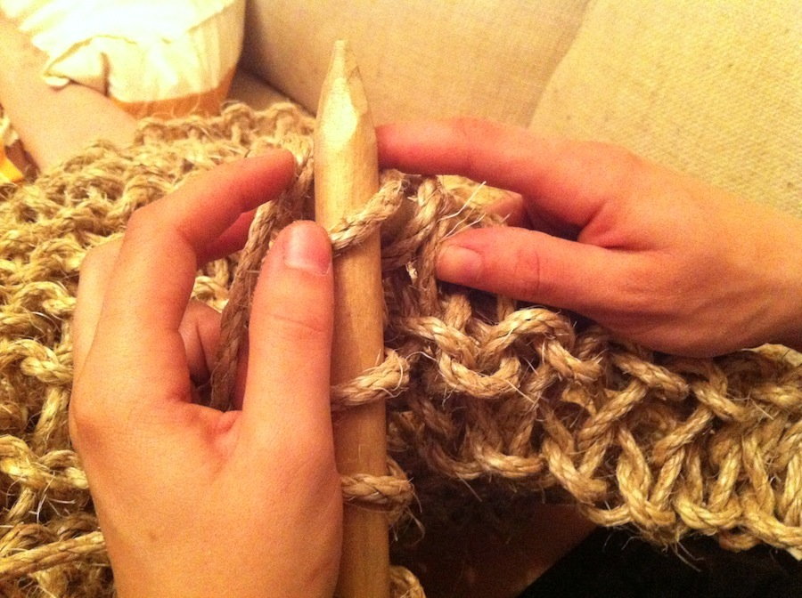 Awkwardly knitting with huge needles.