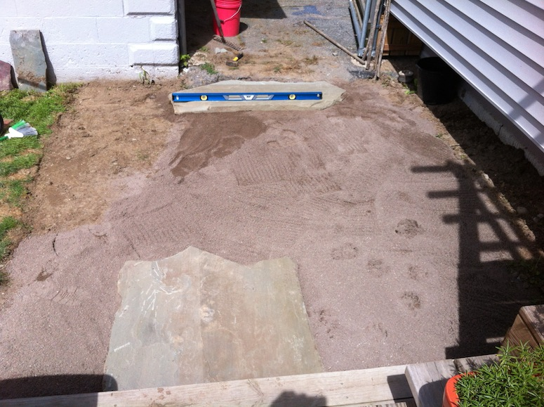 Laying sand underlayment and adjusting the grading.