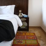 Hand carved headboard, detailed bedside table, and a beautiful Moroccan area rug.