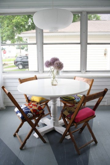 Pretty painted wooden floor serves as the base for a bright sunroom.