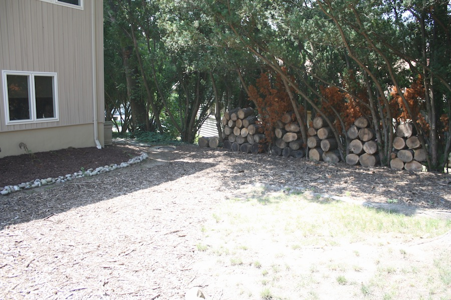 Logs stacked between trees create a natural fence between neighbors.