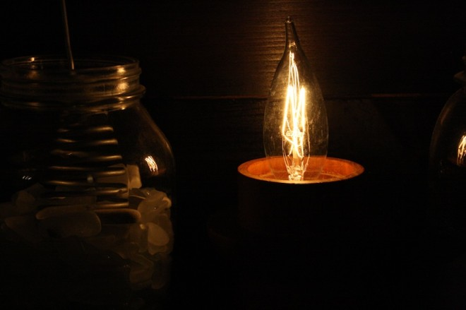 DIY electric candlestick using an upcycled wooden base and length of electrical wire.