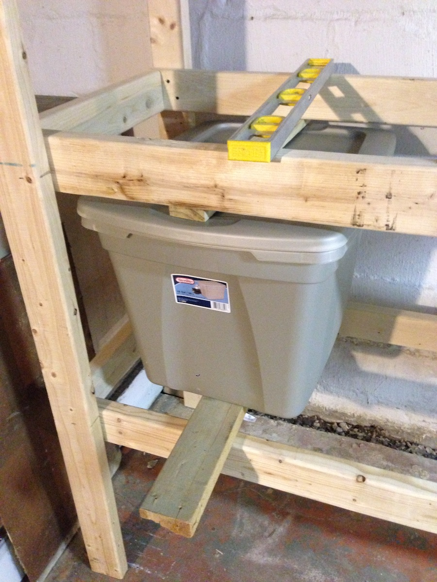 Installing basement shelves to accomodate large plastic bins.
