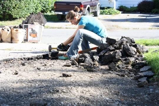 Sledgehammering the asphalt driveway.
