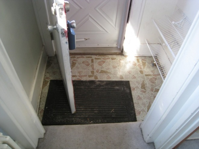 The entryway before, coated with faux-pebble vinyl tile.