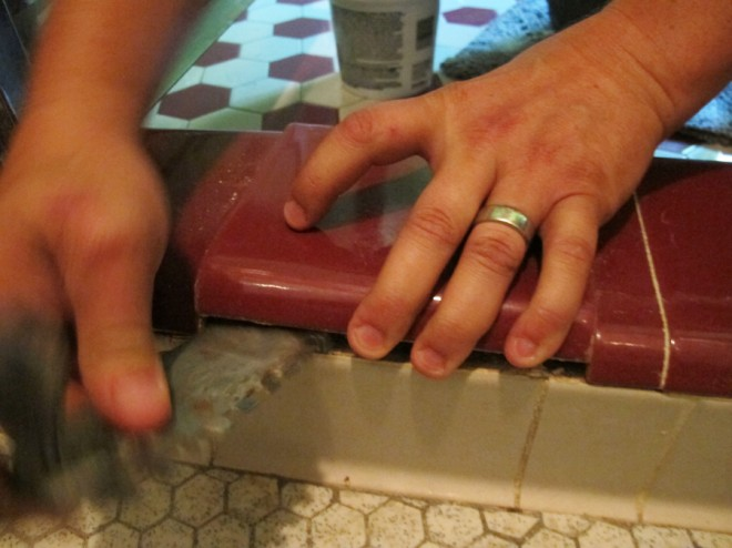 Prying up tiles in the shower to fix leaks.