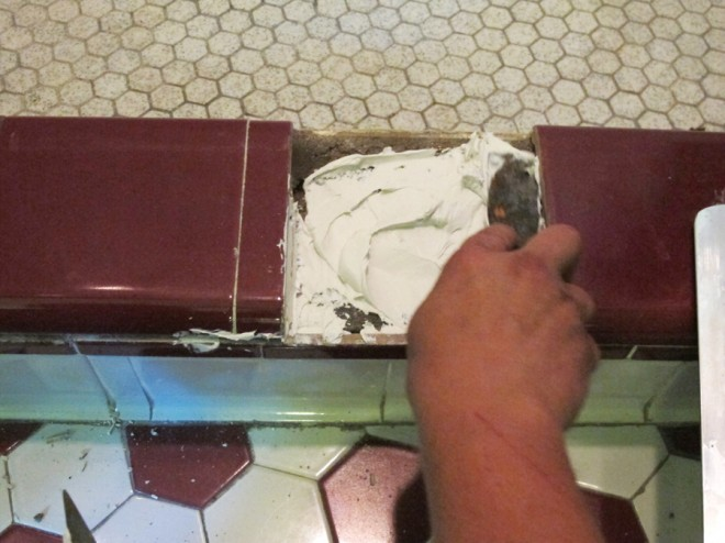 Re-mortaring the threshold tiles in place.