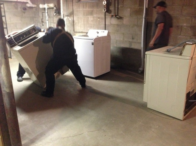 Removing the old washer and dryer.