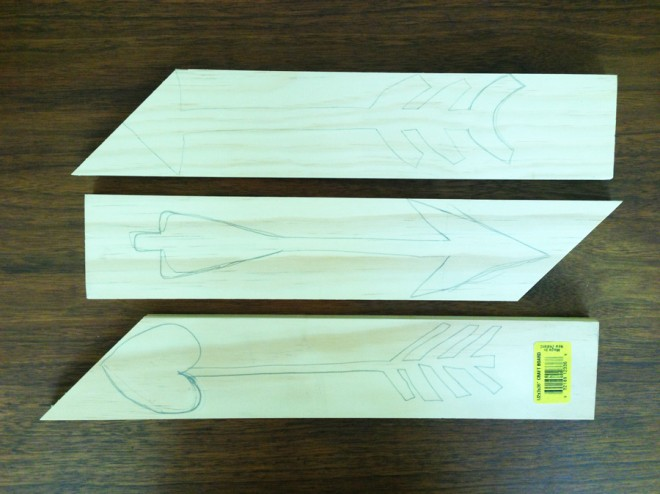 Sketched out very unsymmetrical arrows on craft board scrap wood.